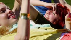 Attractive Teen Friends Lay In The Grass, Blond Girl Throws Flower Petals Stock Footage