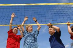 Boys (6-9) at volleyball net, low angle view - stock photo