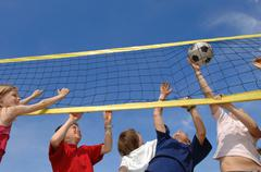 Children (6-9) playing volleyball, low angle view - stock photo