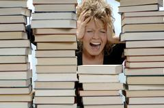 Woman with pile of books, shouting Stock Photos