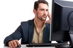 man looking at a computer monitor - stock photo