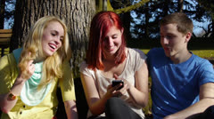 Teen Friends Play With Mobile Phone Under Tree In Park Stock Footage