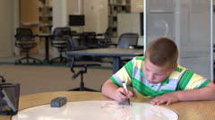 Young boy solving math problem looks up and smiles Stock Footage