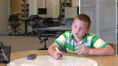 Bored kid working on school work - stock footage