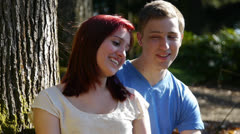 Attractive Teen Couple Sitting Under a Tree In Park Stock Footage