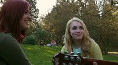 Attractive Girls Watch Handsome Boy Play Guitar In Park Stock Footage