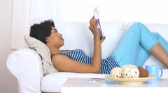 African American woman using tablet computer on couch - stock footage
