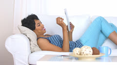 Stock Video Footage of Black woman using her tablet computer in living room