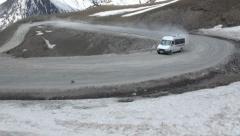 Georgian minivan drives over mountain pass Stock Footage