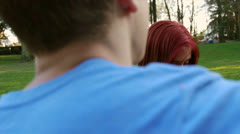 Teen Boy Plays Guitar For Attractive Teen Girl In The Park Stock Footage