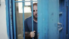 Inmate locked up behind bars Stock Footage