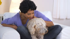African American woman resting chin on pet dog Stock Footage