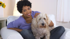 Black woman smiling and petting wheaten terrier Stock Footage