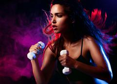 Sexy woman working out with dumbell Stock Photos