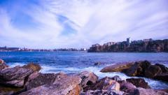 Timelapse of ocean against a rocky coast with a beach in distance 175GYCC NTSC Stock Footage