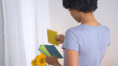 Black woman using paint chips to pick out color for room Stock Footage