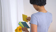 Stock Video Footage of Black woman using paint chips to pick out color for room