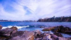 Timelapse of ocean against a rocky coast with a beach in distance 175GYCC PAL Stock Footage