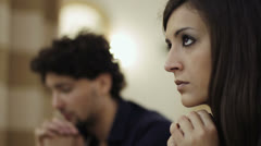 woman in prayer in a church , desperate man in background - stock footage