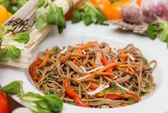 Noodles with vegetables and garnish on white plate Stock Photos