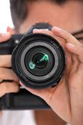 man focusing his camera - stock photo