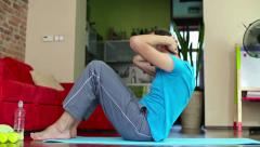 Young man exercising, doing sit-ups in home HD Stock Footage