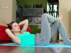 Young woman exercising, doing sit-ups in home, dolly shot NTSC Stock Footage