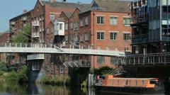 Leeds, two people walk over centenary bridge over river aire, en Stock Footage