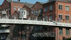 Leeds, couple walk over centenary bridge over river aire, englan Stock Footage