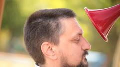 Man speaks to red speaking trumpet Stock Footage