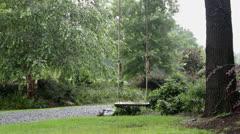 Empty wooden swing in rain on tree Stock Footage