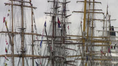 Mast sailing ship with folded sails and colored flags fluttering in the wind.  - stock footage
