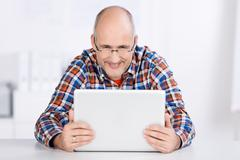 sitting mature man looking at a laptop screen - stock photo