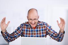 joyful mature man looking at a laptop screen - stock photo