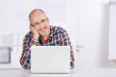 Stock Photo of friendly mature man smiling with a laptop