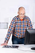 man behind an office desk looking at the computer - stock photo