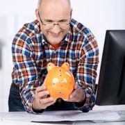 Mature man smiling at a piggy-bank at the office Stock Photos