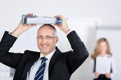 smiling businessman holds a binder on his head - stock photo
