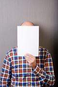 Balding man holding a blank paper in front of face Stock Photos