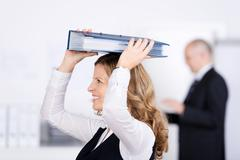 businesswoman with a binder on her head - stock photo