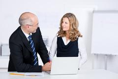 Businesspeople communicating while looking at each other at desk Stock Photos