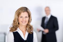 Confident businesswoman smiling with coworker in background Stock Photos
