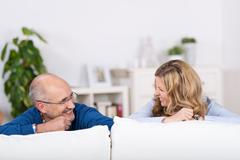 smiling playful couple relaxing on a sofa - stock photo