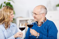couple toasting red wineglasses while looking at each other - stock photo