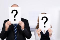 Businesspeople holding question mark signs on placard in front o Stock Photos