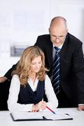 businesswoman pointing to paperwork - stock photo