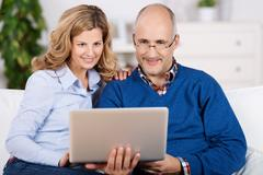 happy couple reading information on their laptop - stock photo