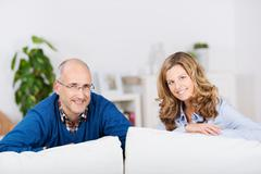 Couple leaning on sofa at home Stock Photos