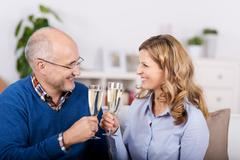 couple toasting champagne flutes while looking at each other - stock photo