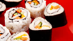 Maki Rolls and California rolls on red plate Stock Footage